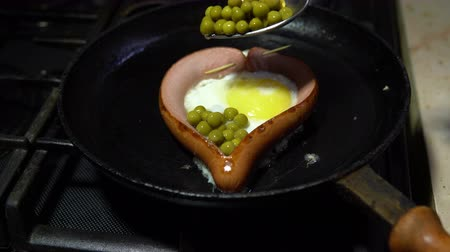peas : Preparation of fried eggs and sausages in the form of a heart on a hot frying pan in the morning for breakfast. Adding green peas to food.