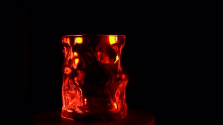 quartilho : The glass goblet turns under a red backlight on a black background, seamless looping shot.
