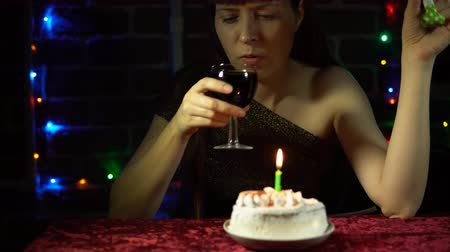 assobio : Sad attractive woman celebrates the holiday, she sits at a table with a cake, a glass of wine and blowing a colorful party horn.