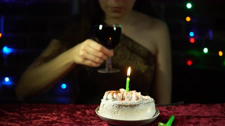 borospohár : A lonely attractive woman sits at a festive table with a cake and a burning candle, she drinks red wine in the evening. Stock mozgókép