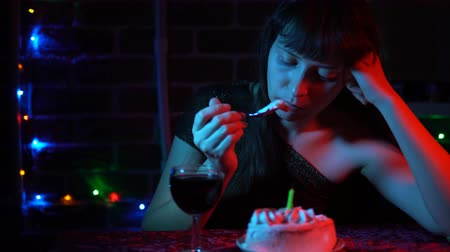 elegant dessert : Young attractive woman in a shiny dress drinking wine sitting at a table with a festive cake. Sad brunette celebrates the holiday. Stock Footage