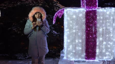mobilitás : Young happy woman in a gray warm jacket is getting a message using the application in a smartphone standing next to a large white sparkling glowing gift with a red bow.