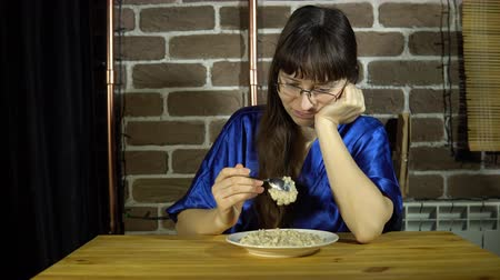 kabuksuz tahıl : A young, sleepy woman with glasses unwillingly intends to eat oatmeal, a brunette sitting at a wooden table next to a brick wall.