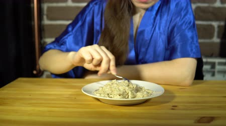 kabuksuz tahıl : A woman in a blue robe a spoon is the porridge in a white plate, then pushes it away from herself. Stok Video