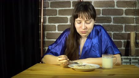 kabuksuz tahıl : A young woman in a blue robe eats oatmeal for breakfast next to a brick wall