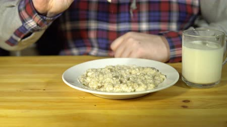 kabuksuz tahıl : An unknown man in a plaid shirt drives a spoon on a plate of oatmeal, raises the porridge and sharply throws back. Stok Video