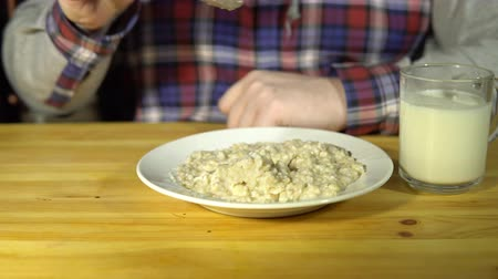 kabuksuz tahıl : Close-up of a male hand is driving a spoon on a plate with oatmeal. The man of the porridge and takes out a glass of milk