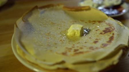 vaj : Close-up someone using a knife smears butter over a hot ruddy appetizing pancake, 4k. Stock mozgókép
