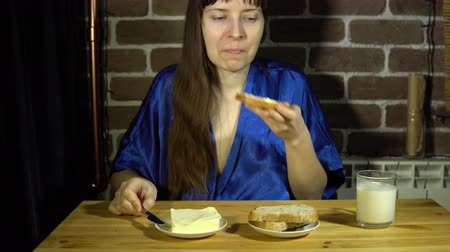 roucho : A happy young woman in a blue smock spreads butter on a slice of multigrain bread, then bites off a piece and smiles looking into the camera, the brunette sits next to a brick wall, 4K.