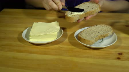 tereyağı : Close-up of female hands preparing a sandwich, using a knife butter spread on whole grain bread, 4K. Stok Video