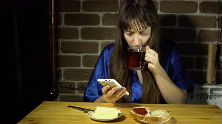 reçel : A young sleepy woman in a blue robe browses the video on her smartphone and drinks tea, sitting next to a brick wall, 4K.