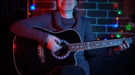 strum : A young woman in a gray sweater plays on an acoustic guitar next to a brick wall indoors. The musician learns new methods of sound extraction.