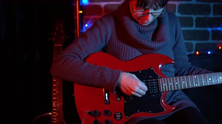 гитара : A nice young woman in a gray sweater plays on a red electric guitar in the evening at a brick wall. Стоковые видеозаписи