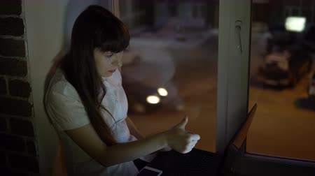 secretária : A business woman sits on the windowsill and raises his thumb up in front of the laptop during a videoconference evening, outside the window in the street a road with a busy traffic.