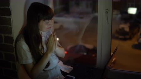 késő : A business woman is sitting on the windowsill and and applauds in front of the laptop during a video conference evening, outside the window in the street a road with a busy traffic.