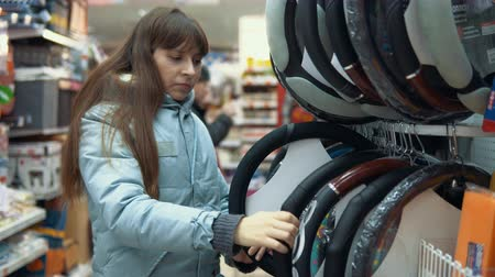 removable : A young woman chooses a case for steering the car in the department of accessories and spare parts for autos.