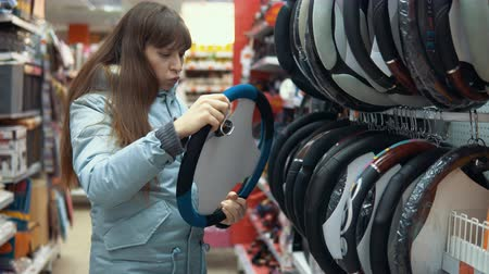 sobressalente : A young woman chooses a case for steering the car in the department of accessories and spare parts for autos.