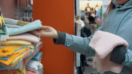terry : A young woman chooses a terry towel in the textile department of the supermarket. Stock Footage