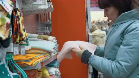 terry : Customer womans chooses a terry towel in the textile department of the supermarket.