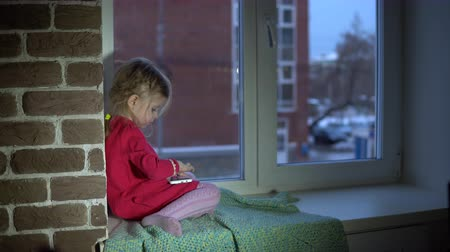 клетчатый : Little cute girl in pink dress is studying and playing in app on white smartphone, sitting on a multi-colored plaid on the windowsill, outside the window on the street a brick office building.