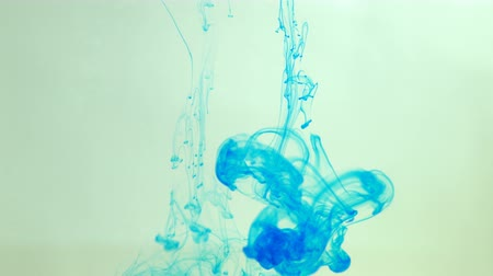 toner : Close-up of droplets and splashes of blue ink moving, mixed in liquid, abstract background.