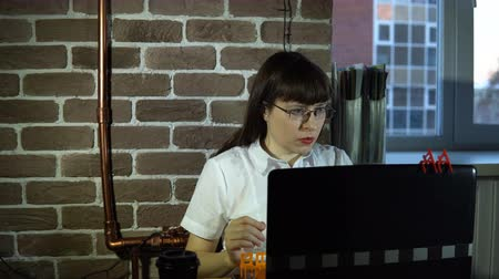 supervisor : Young business woman in modern office working at desk on laptop, completing workday twilight outside the window. The manager plans a career by placing small chairs over the computer monitor, 4K.