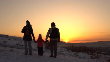 szülői : Happy family of three people standing on a mountain holding hands in winter at sunset.