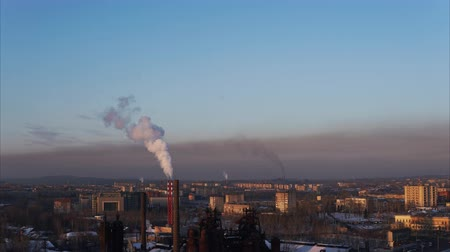 dioxid : Time lapse cityscape with smoking pipes against the cold winter sky, busy traffic on city roads at sunset.