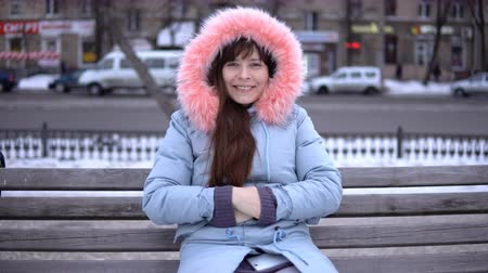автобус : Portrait of a young happy woman in a gray coat sitting on a bench outside on a winter day.