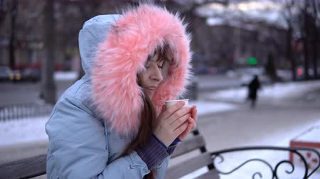warms : A young woman in a gray warm jacket drinking a cup of coffee, a brunette sitting on a bench outside in the winter. Stock Footage