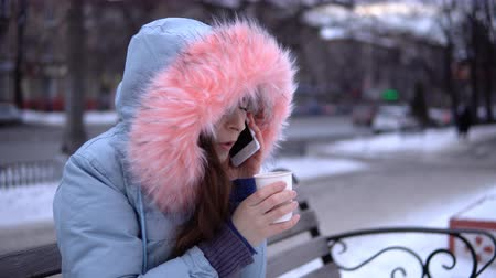 snow caps : A young woman in a gray warm coat talking on the phone and drinking hot tea or coffee from a paper cup, a brunette sitting on a bench outside in the winter. Stock Footage