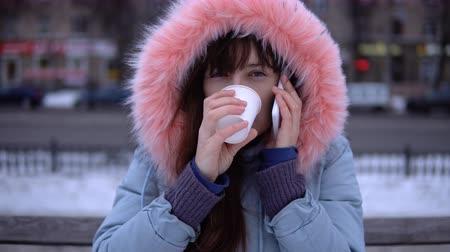 warms : A young woman in a gray warm jacket talking on the phone and drinking hot tea or coffee from a cup, a brunette sitting on a bench outside in the winter.