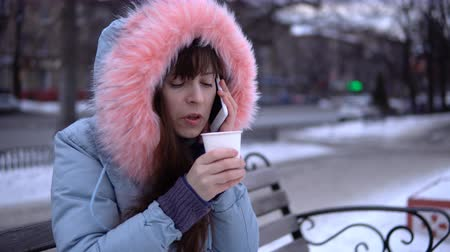 snow caps : A young woman in a gray warm jacket talking on the phone and drinking hot tea or coffee from a cup, a brunette sitting on a bench outside in the winter.