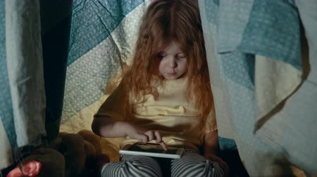 el feneri : A little girl in pajamas uses the phone while sitting in a tepee tent in the playroom in the evening. Stok Video