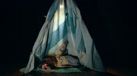 mobile game : A little girl in pajamas is lying down and using the phone in the wigwam. Stock Footage