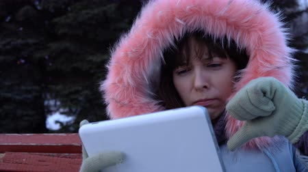 snow caps : Portrait of a young unhappy woman using a digital tablet and sitting on a bench in a city park next to a Christmas tree on a snowy winter day, she shows the interlocutor a sign of the thumb down. Stock Footage