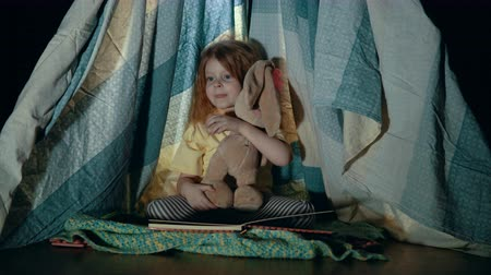rabbits : A little girl in pajamas is sitting and reading a book to her toy in a wigwam.