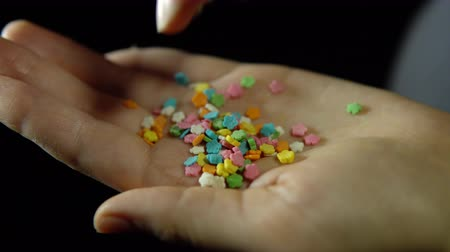 sifting : Close-up of a human hand, fingering a handful of confectionery powder in the form of a flower in the palm of a hand against a black background, unrecognizable person.