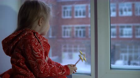 hůlky : A little pretty girl in a red fleece sweatshirt sits on the windowsill looking at the snowy cityscape. The child waves with a magic wand.