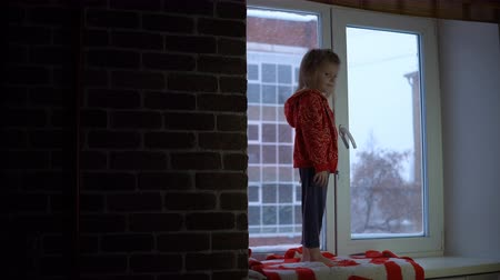 sill : A little pretty girl in a red fleece sweatshirt stand on the windowsill looking at the snowy cityscapee. A child points with a finger snowflakes flying outside the window. Stock Footage