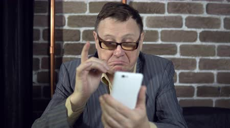 изумление : A busy elderly businessman in glasses uses a white smartphone, typing messages, reads articles, is surprised at the news.