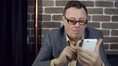 tárcsázás : A busy elderly businessman in glasses uses a white smartphone, typing messages, reads articles, is surprised at the news.