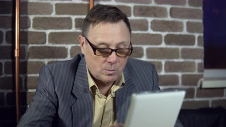 bewilderment : Senior businessman in eyeglasses is working with a digital tablet at the room with a brick wall. Stock Footage