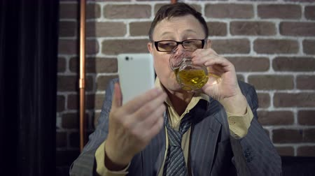 bêbado : Portrait of a senior businessman in glasses using a white smartphone, holding alcohol in a glass, then drinking, sitting at a table by the brick wall.