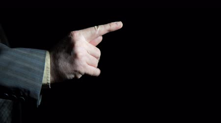 sleeve : Hand of a businessman shows a figs gesture on a black background, close up shoot.