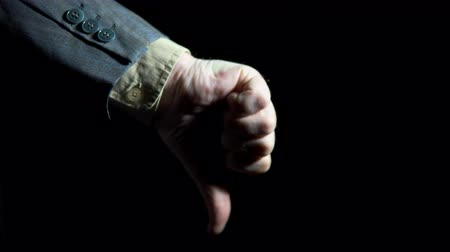 disapprove : A businessmans hand shows a thumb gesture down on a black background, close up shoot.