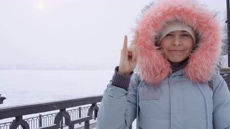 růžky : Female blogger shows gesture horns and looks at the camera. Portrait of a young happy woman in a warm gray parka outdoors against a background of a frozen city pond in a snowfall in winter.
