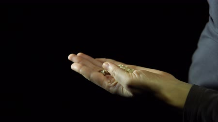 kabuksuz tahıl : Close-up of a human hand, fingering a handful of oatmeal in the palm of a hand against a black background, unrecognizable person .. Stok Video