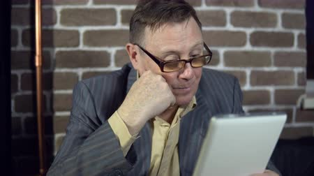 bewilderment : Senior businessman in eyeglasses is working with a digital tablet at the office with a brick wall.