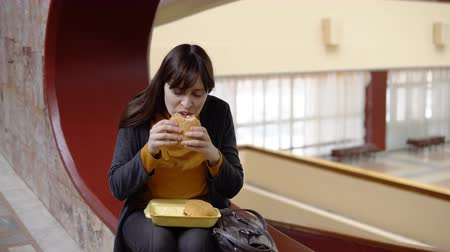 фрикаделька : Young attractive woman eats a delicious hamburger in the office during lunch. The problem of healthy eating.